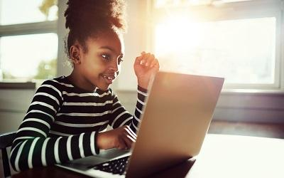 Young girl sitting at a desk using a laptop