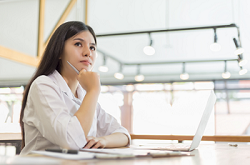Image of a woman working at a laptop looking up thoughtfully