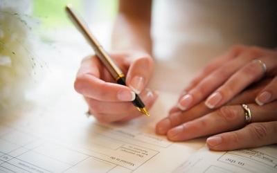 Hands signing wedding registration