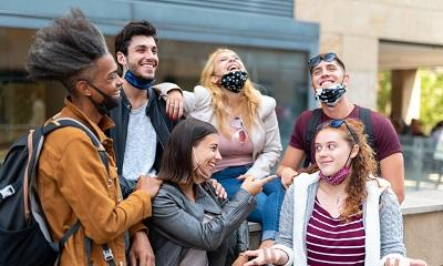 Image of young people not wearing masks properly and laughing MandriaPix/Shutterstock