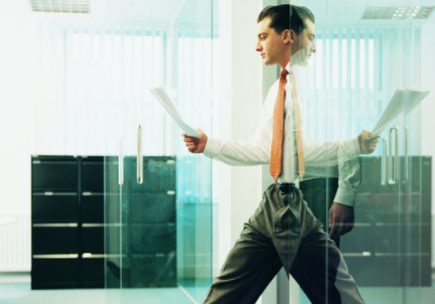 businessman walking out of office with report