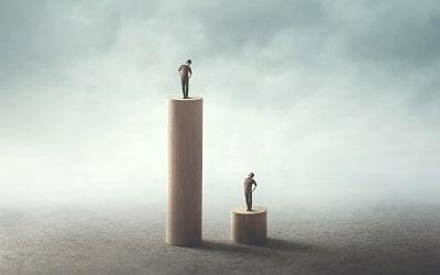 Inequality between people concept - one person on a high block looking down on someone on a much lower one