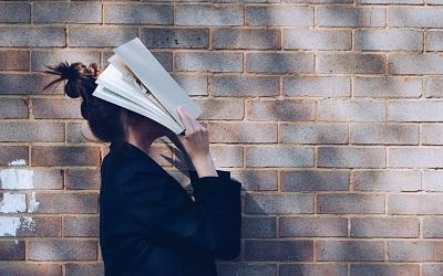 Photo of a stressed student with a book on her face